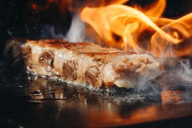 Bbq roast marinated baby zurück schweinerippennahaufnahme auf heißem loderndem grill Premium Fotos