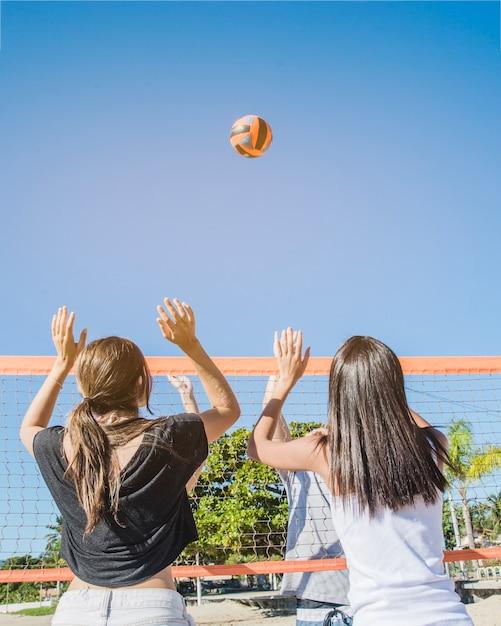 Beach-volleyball-szene mit mädchen im netz Kostenlose Fotos