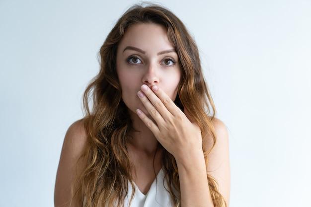 Beängstigend hübsche junge frau, die mund mit der hand bedeckt Kostenlose Fotos