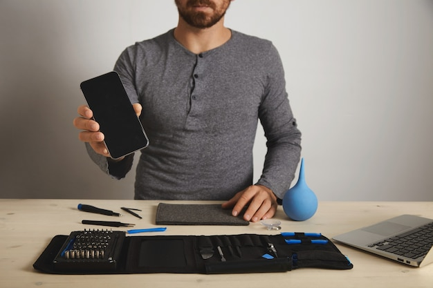 Bearded professional zeigt repariertes festes smartphone nach dem austausch des service, über seinen spezifischen werkzeugen in der toolkit-tasche in der nähe des laptops auf einem weißen holztisch Kostenlose Fotos
