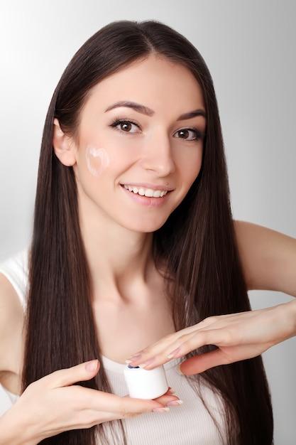 Beauty hautpflege. schöne frau, die kosmetische gesichtscreme aufträgt Premium Fotos