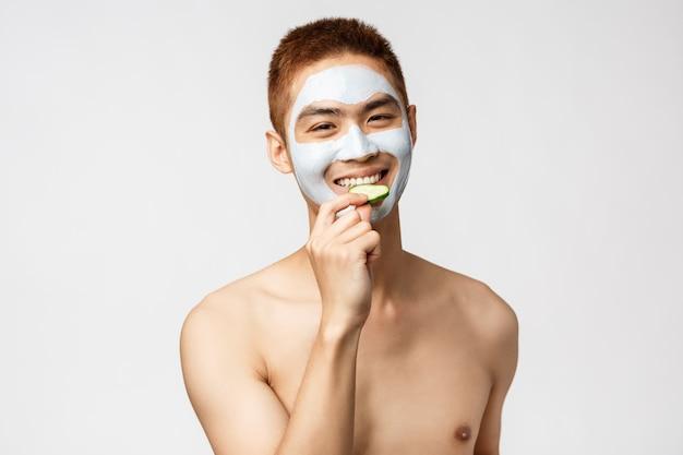 Beauty-, hautpflege- und spa-konzept. hübscher asiatischer mann mit nacktem torso in kosmetischer gesichtsmaske, essgurke und lächelnd, entspannend auf freizeit im salon, stehende weiße wand Premium Fotos