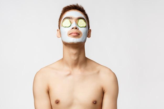 Beauty-, hautpflege- und spa-konzept. porträt des gutaussehenden entspannten asiatischen mannes mit nacktem oberkörper, der sich mit gesichtsmaske und gurken auf den augen entspannt, kopf anhebt, trost fühlt, stehende weiße wand Premium Fotos