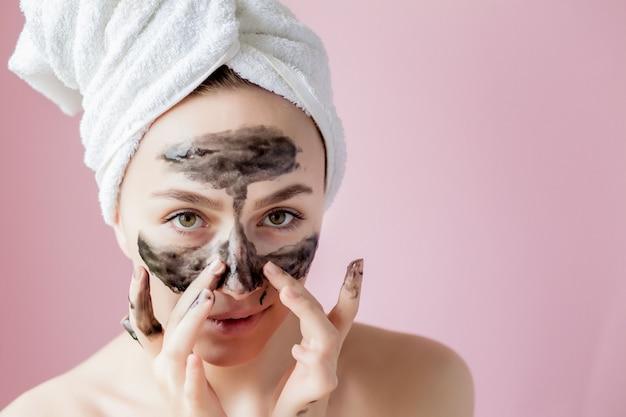 Beauty-kosmetik-peeling. nahaufnahme-schöne junge frau mit schwarzem ziehen weg maske auf haut ab Premium Fotos