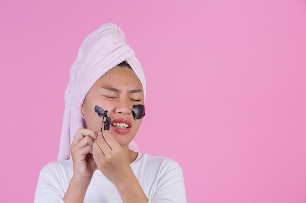 Beauty kosmetisches peeling. junge frau mit schwarzem ziehen weg maske auf kosmetischem hautpflege-schalenprodukt der haut auf gesicht auf einem rosa ab. Kostenlose Fotos