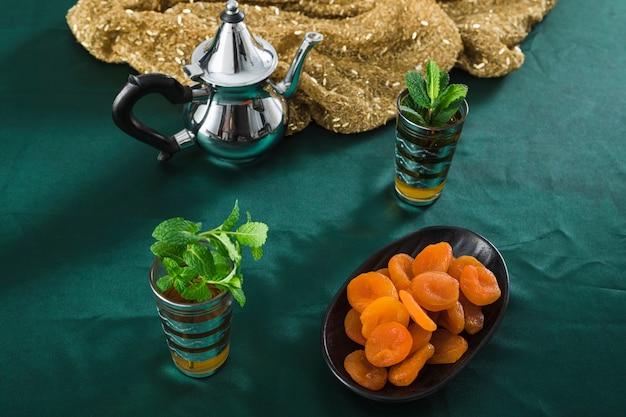 Becher des getränks nahe silberner teekanne und getrockneten aprikosen Kostenlose Fotos
