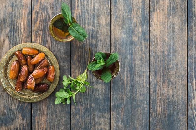 Becher des getränks nahe trockenfrüchten auf saucer Kostenlose Fotos