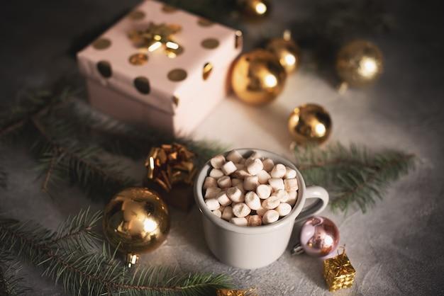 Becher für modell nahe weihnachtsbaum und geschenkboxen Premium Fotos
