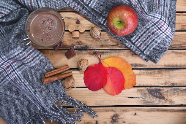Becher heiße schokolade mit schal und rotem apfel im winter und auf einem holztisch Premium Fotos