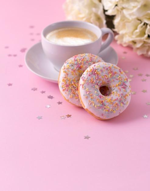 Becher heißer cappuccino und zwei schaumgummiringe mit blumen auf rosa Premium Fotos