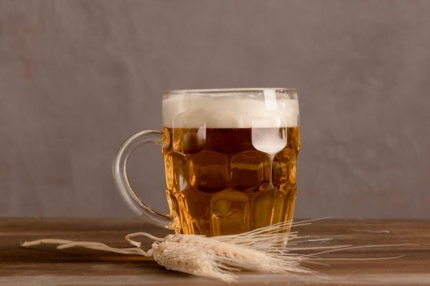 Becher helles bier mit weizen auf holztisch Kostenlose Fotos