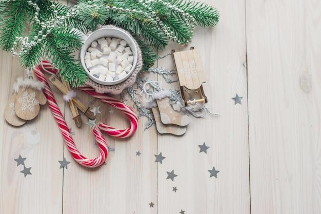 Becher marshmallows und zuckerstangen, umgeben von weihnachtsschmuck auf dem tisch Kostenlose Fotos