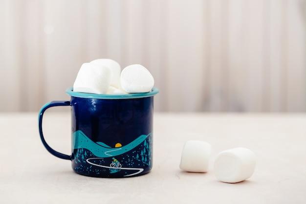 Becher mit leckeren marshmallows auf hellem holztisch, nahaufnahme. hintergrundkonzept des winterlebensmittels. Premium Fotos