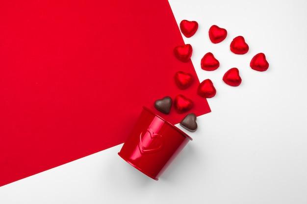 Becher mit schokoladenherzen auf rotem hintergrund. flache laienzusammensetzung. romantisch, st. valentinstag-konzept Premium Fotos