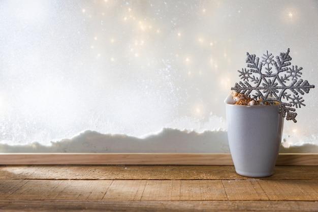 Becher mit spielzeugschneeflocke auf hölzerner tabelle nahe bank des schnees und der feenhaften lichter Kostenlose Fotos