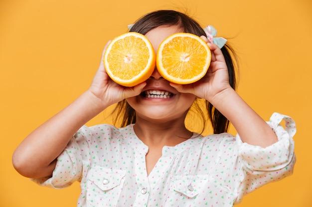 Bedeckungsaugen des kindes des kleinen mädchens mit orange. Kostenlose Fotos