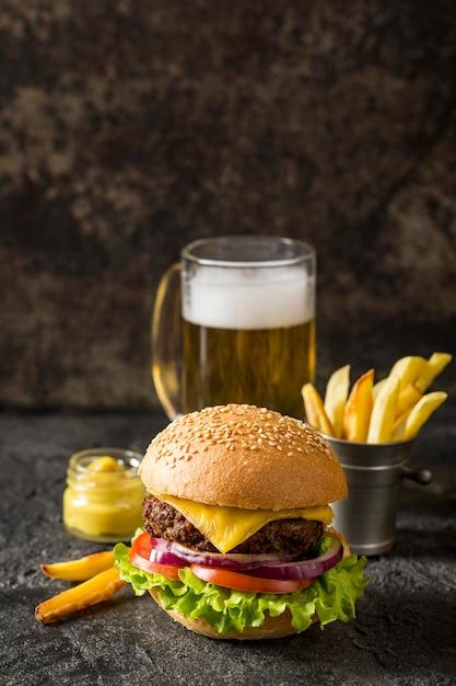 Beef burger, pommes und sauce von vorne mit bier und kopierraum Kostenlose Fotos
