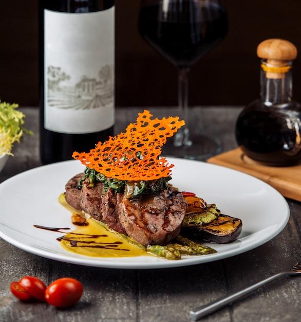 Beefsteakscheiben garniert mit kräutern und sauce, serviert mit gegrilltem gemüse Kostenlose Fotos