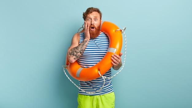 Beeindruckter rothaariger mann hat einen nervösen gesichtsausdruck, schwimmt zum ersten mal im meer und benutzt eine ringboje Kostenlose Fotos