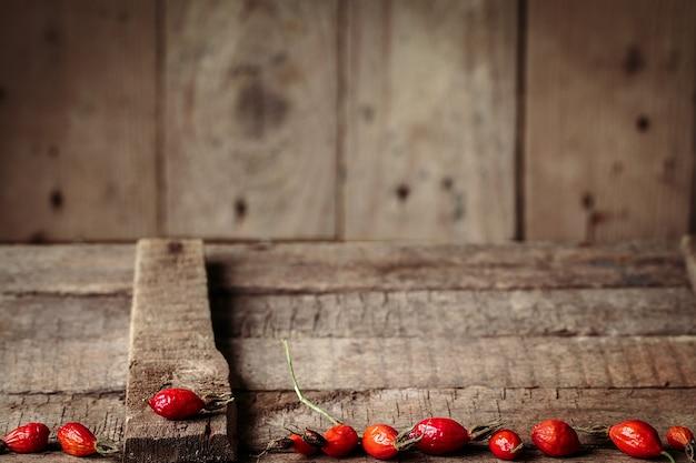 Beeren einer heckenrose auf einem holztisch Premium Fotos