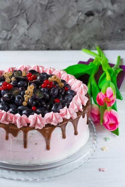 Beerenkuchen mit sahne, trauben, rote johannisbeere, weiße johannisbeere. rosa tulpen Premium Fotos