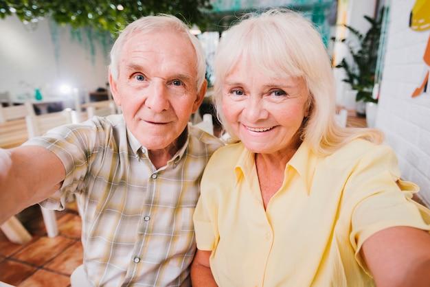 Begeisterte ältere paare, die das sitzen im café und das schießen von selfie umarmen Kostenlose Fotos