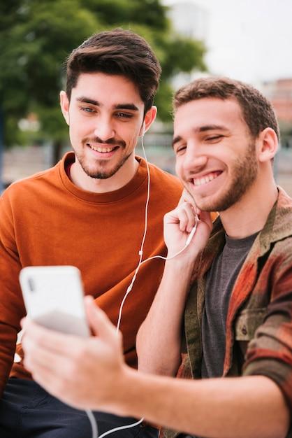Begeisterte homosexuelle paare in den kopfhörern hörend musik auf mobile Kostenlose Fotos
