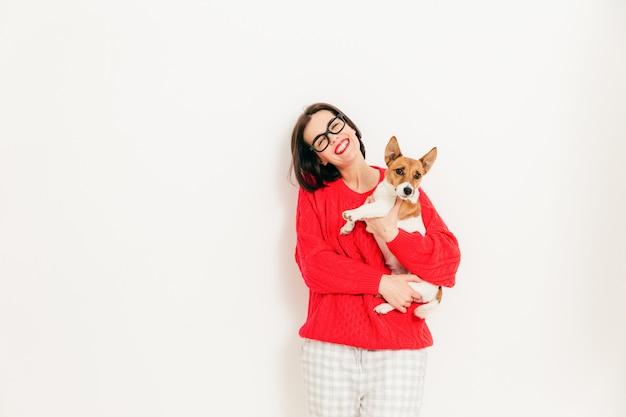 Begeisterte kaukasische frau trägt jack russell-terrierhund, trägt schauspiele und rote strickjacke, genießt freizeit mit lieblingshaustier Premium Fotos