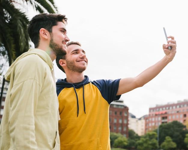 Begeistertes homosexuelles paar, das selfie auf straße schießt Kostenlose Fotos