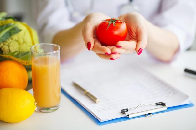 Begriffsfoto eines weiblichen ernährungswissenschaftlers with fruits on the desk Premium Fotos