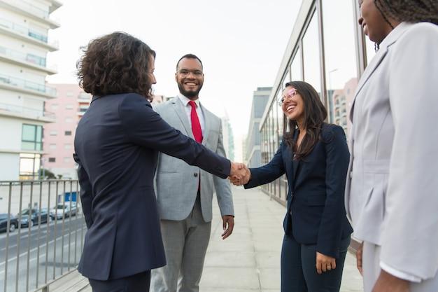Begrüßende partner des glücklichen weiblichen managers draußen Kostenlose Fotos