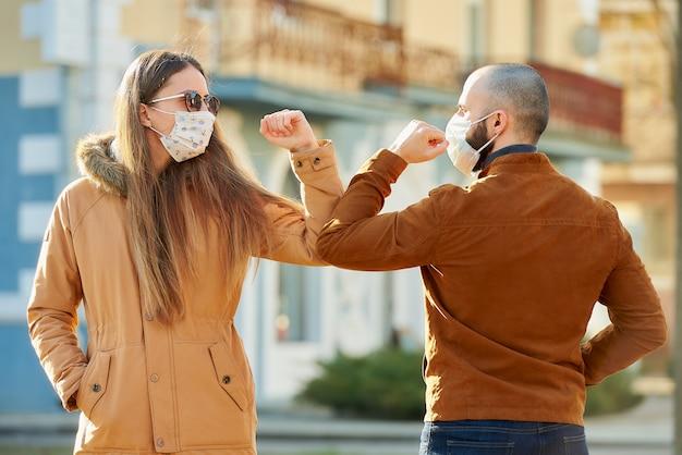 Begrüßung des ellenbogens, um die ausbreitung des coronavirus (covid-19) zu vermeiden. ein mann und eine frau in medizinischen gesichtsmasken treffen sich mit bloßen händen auf der straße. anstatt mit einer umarmung oder einem händedruck zu grüßen, stoßen sie an die ellbogen. Premium Fotos