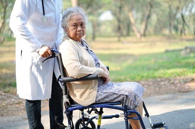 Behandeln sie hilfe und sorgfalt asiatischen älteren frauenpatient der alten dame, der auf rollstuhl am park sitzt. Premium Fotos