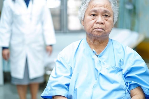 Behandeln sie hilfe und sorgfalt asiatischen älteren oder älteren frauenpatient der alten dame, der auf rollstuhl sitzt. Premium Fotos