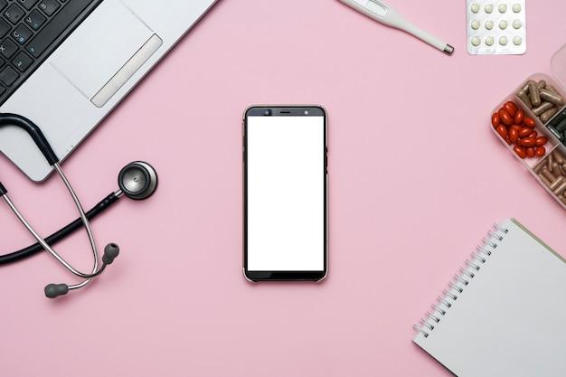 Behandeln sie rosa schreibtischtabelle mit leerem smartphone, stethoskop, medizin, notizbuch. Premium Fotos
