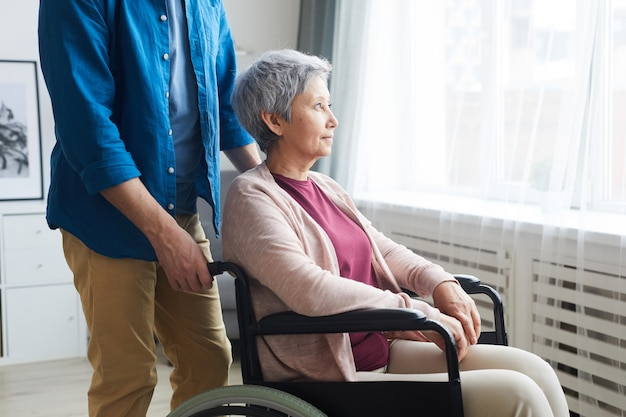 Behinderte ältere frau, die im rollstuhl sitzt und durch das fenster mit der in der nähe stehenden pflegekraft schaut Premium Fotos