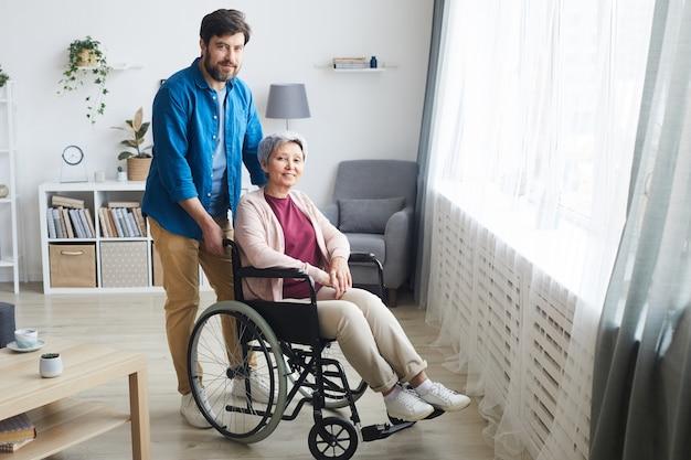 Behinderte ältere frau sitzt im rollstuhl und lächelt in die kamera mit mann, der hinter ihr steht, sie sind im raum zu hause Premium Fotos