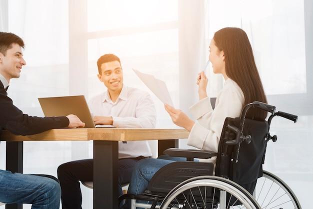 Behinderte junge geschäftsfrau, die auf dem rollstuhl sich bespricht mit seinem männlichen kollegen im büro sitzt Kostenlose Fotos