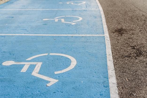 Behindertenparkschild auf dem boden gemalt, beispiel für die integration von menschen mit eingeschränkter mobilität. Premium Fotos