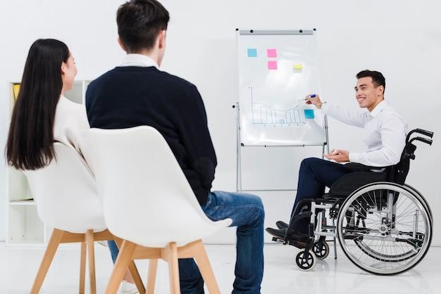 Behinderter junger geschäftsmann, der dem geschäftskollegen darstellung gibt Kostenlose Fotos