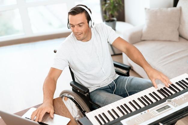Behinderter mann, der lied mit synthesizer komponiert Premium Fotos