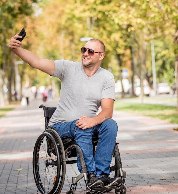 Behinderter mann im rollstuhl an der parkgasse benutzen ein smartphone Premium Fotos