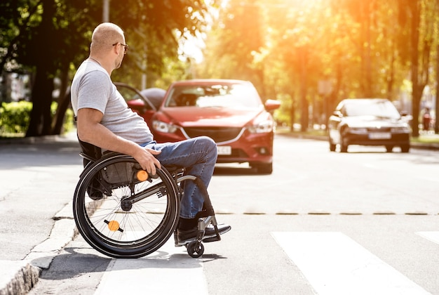 Behinderter mann im rollstuhl, der straßenstraße kreuzt Premium Fotos