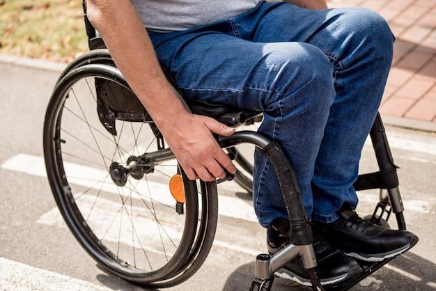 Behinderter mann im rollstuhlspaziergang an der parkgasse Premium Fotos