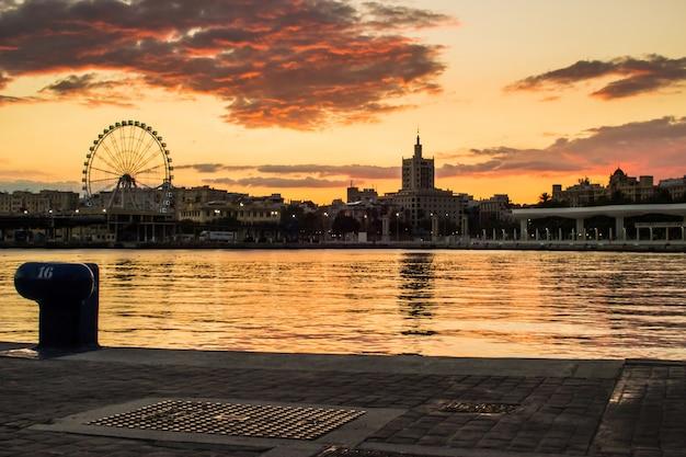 Bei sonnenuntergang hafen mit dem hintergrund riesenrad Kostenlose Fotos