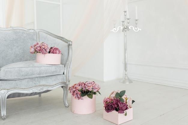 Beige rosa purpurroter pfingstrosenblumenstrauß der schönen blume auf boden im rosa kasten im hellen weißen raum Kostenlose Fotos