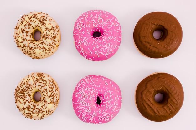 Beige; rosa und brauner donut auf weißem hintergrund Kostenlose Fotos