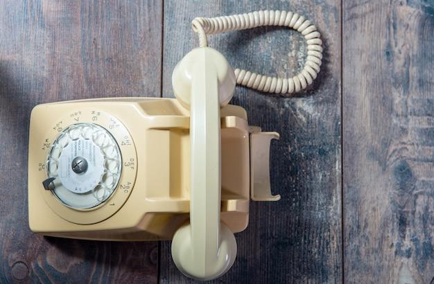 Beiges altes telefon auf dem holz Premium Fotos