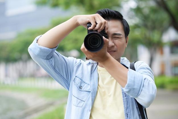 Beiläufig gekleideter asiatischer mann, der fotos im park macht Kostenlose Fotos