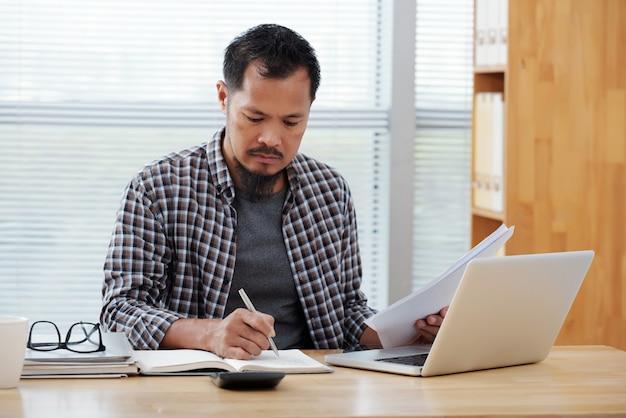 Beiläufig gekleideter asiatischer mann, der im büro arbeitet, in notizbuch schreibt und dokumente verwahrt Kostenlose Fotos